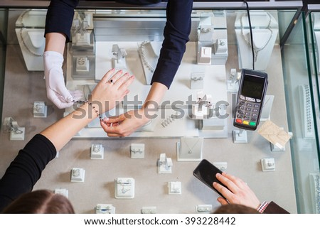 Young woman trying on golden bracelet, man going to pay with credit card