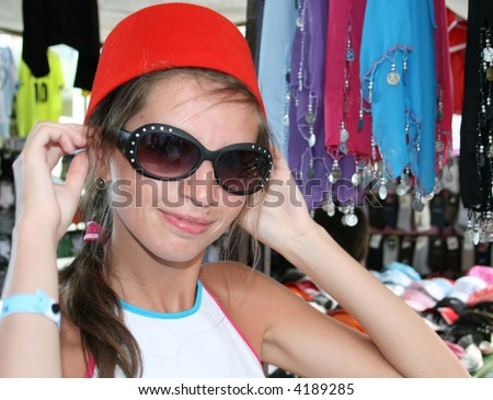 Young woman trying on the traditional hat worn in Turkey - fez - stock photo