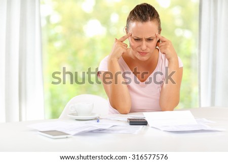 Young woman trying to figure out a way through a rough financial crisis - stock photo