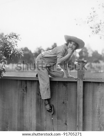 Young woman trying to get over a wooden fence with a fruit in her hands - stock photo