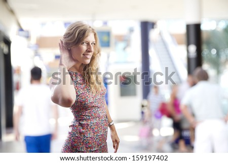young woman trying to listen in a shopping center - stock photo