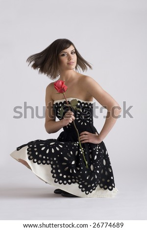 Young woman turns head and flips hair while holding a rose and wearing black and white dress - stock photo