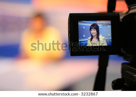 Young woman TV reporter, smiling and presenting the news, view in video camera display - stock photo