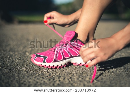Young woman tying laces of running shoes before the outdoor jogging. - stock photo