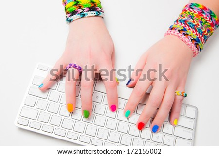 Young woman typing on a computer keyboard wearing loom bracelets on her hands. Close up. Young fashion concept - stock photo