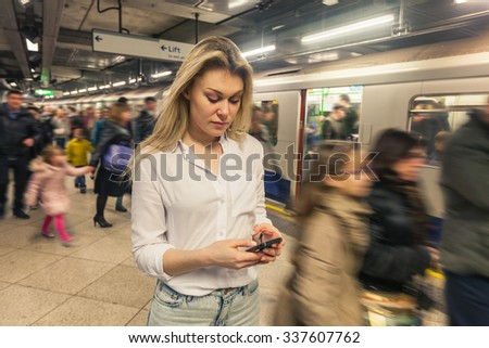 Young woman typing on smart phone at tube station in London. She wears a white shirt and she is looking at the phone. There are a lot of blurred people walking on the platform and boarding the train. - stock photo