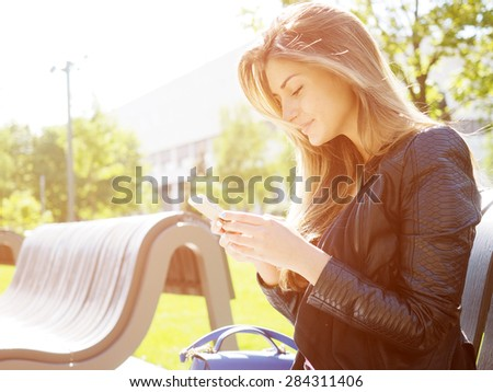 Young woman typing sms message. Natural sunflare - stock photo