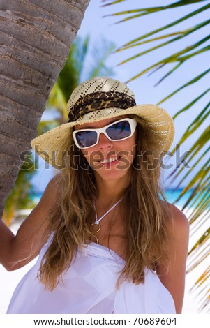young woman under a palm on a tropical beach - stock photo