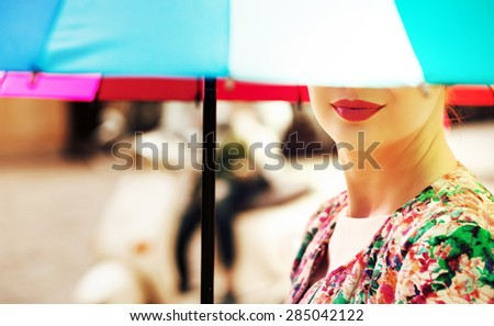 Young woman under an colorful umbrella - stock photo