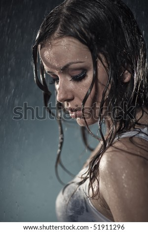 Young woman under the rain. Water studio photo. - stock photo