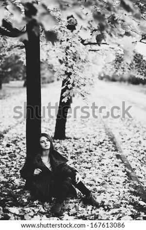 Young woman under tree. Black and white film style colors. - stock photo