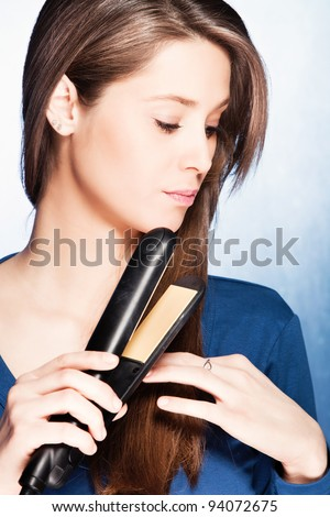 young woman use hair straightener iron, studio shot - stock photo