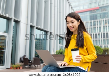Young woman use of the laptop computer and enjoy her coffee - stock photo