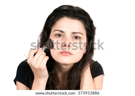 Young woman uses a cosmetic brush to apply blush makeup to her face. - stock photo