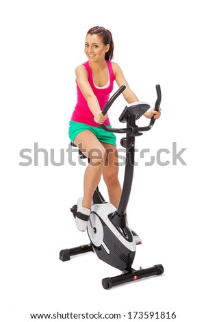 Young woman uses stationary bicycle trainer. - stock photo