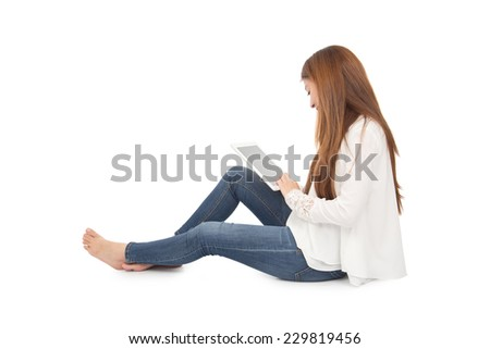 young woman using a digital tablet against a white background - stock photo