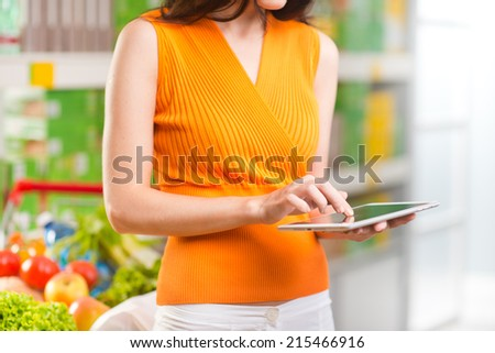 Young woman using a digital tablet at store with supermarket shelves on background. - stock photo