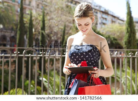 Young woman using a digital tablet pad while visiting a city on vacation and carrying shopping paper bags during a sunny day. - stock photo