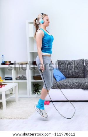 Young woman using a jump rope at home