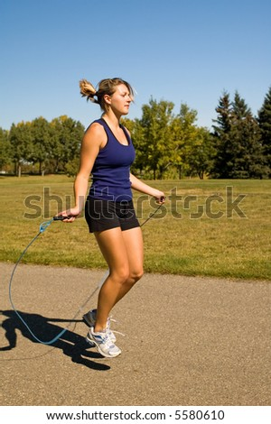 Young woman using a jump rope in a park. - stock photo
