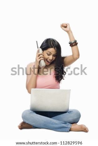 Young woman using a laptop and talking on a cordless phone - stock photo