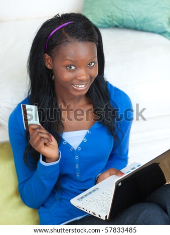 Young woman using a laptop sitting on bed against a white background - stock photo