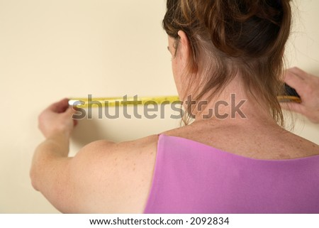 Young woman using a measurement tape