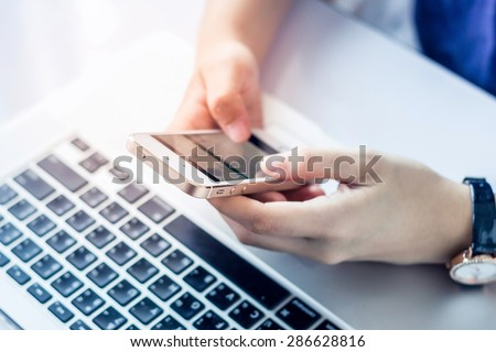Young woman using a mobile phone and laptop - stock photo