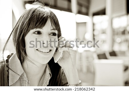 Young woman using a mobile phone in a Pub. - stock photo