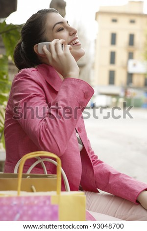 Young woman using a mobile phone while sitting down with shopping bags outdoors. - stock photo
