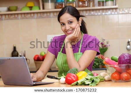 Young woman using a tablet computer in her kitchen - stock photo