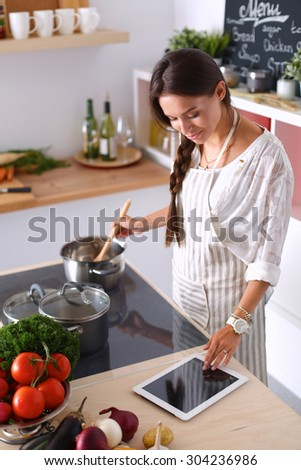Young woman using a tablet computer to cook in her kitchen . - stock photo