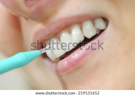 young woman using an interdental brush - stock photo
