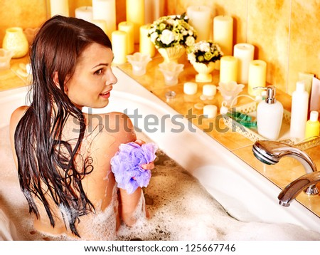 Young woman using bath sponge in bathtub. - stock photo