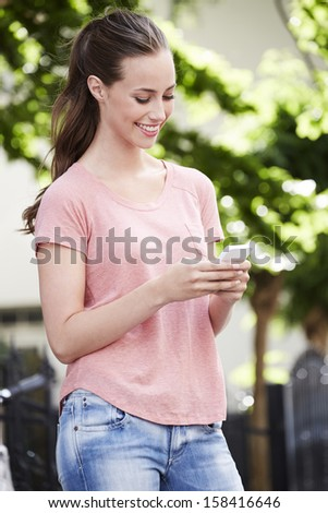 Young woman using cellphone outdoors - stock photo