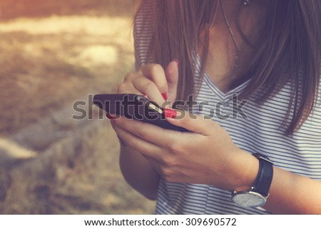 Young woman using cellphone outdoors. - stock photo