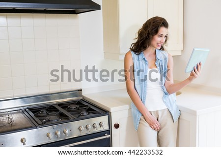 Young woman using digital tablet in kitchen at home