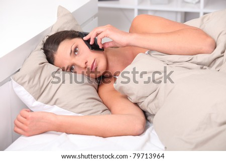 Young woman using her cellphone in bed - stock photo