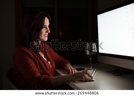 Young woman using her computer at night