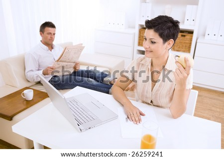 Young woman using laptop computer at home, smiling. Her boyfriend reading newspaper in the background. Selective focus on the woman.
