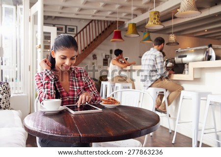 Young woman using laptop in a cafe - stock photo