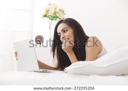 Young woman using laptop in bed - stock photo