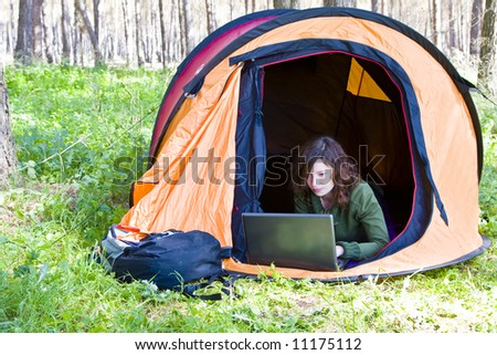 Young woman using laptop in the middle of the forest - stock photo