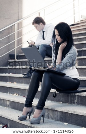 Young woman using laptop on the steps - stock photo