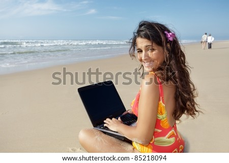 young woman  using laptop on wild beach - stock photo