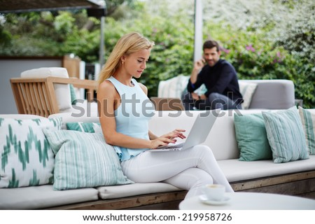 Young woman using laptop pc for work, young serious man talking on mobile phone sitting in the same place on background, man having sympathy to attractive woman seated near in the terrace of same bar - stock photo