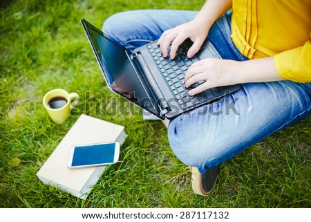 Young woman using laptop while sitting in a park - stock photo