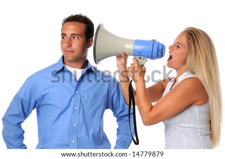 Young woman using megaphone to communicate to uninterested man - stock photo