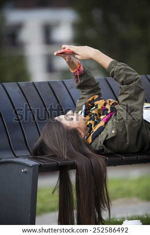 Young woman using mobile phone in park - stock photo