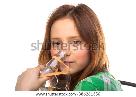 Young woman using nebulizer mask for respiratory inhaler Asthma Treatment isolated on a white background. Close up view. - stock photo